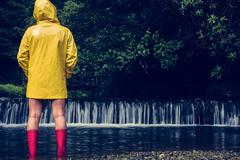 Woman in yellow raincoat and red gumboots looking at scenic waterfall Stock Photos