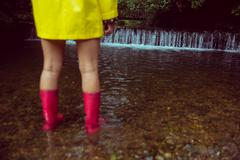 Woman in yellow raincoat and red gumboots in water Stock Photos