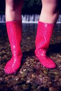 Low section of a woman in pink gumboots on pebbles Stock Photos