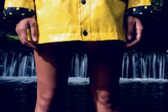 Woman in yellow raincoat against scenic waterfall Stock Photos