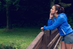 Thoughtful healthy woman standing on footbridge Stock Photos