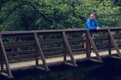 Smiling healthy young woman standing on footbridge Stock Photos