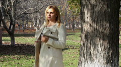Young woman walking in autumn park - stock footage