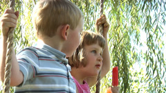 Two children sitting on a swing eating popsicles Stock Footage