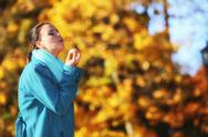 Stock Photo of young woman girl having fun blowing soap bubbles in park