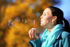 Young woman girl having fun blowing soap bubbles in park Stock Photos