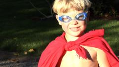 Young boy putting on superhero costume Stock Footage
