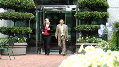 Businesspeople walk out of office building Stock Footage