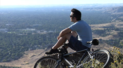 Mountain biking man takes a break Stock Footage