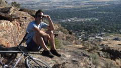 Mountain biking man takes a break Stock Footage