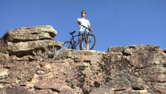 Mountain biker at edge of cliff Stock Footage