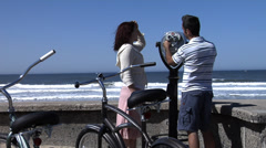 Couple at beach looking through viewer - stock footage