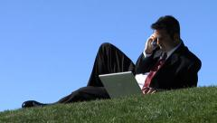 Businessman outdoors with laptop and cell phone Stock Footage