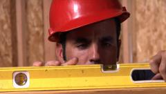 Construction worker looking at a level Stock Footage