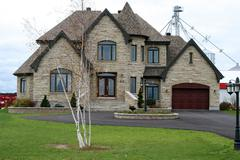 Executive stone house with turret and circular driveway - stock photo