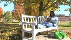 Girl sitting on bench listening to mp3 player - stock footage