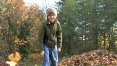 Young boy throwing leaves at camera Stock Footage