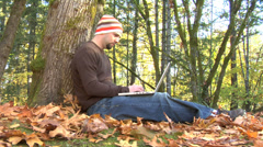 Man sitting in outdoor autumn setting using laptop Stock Footage