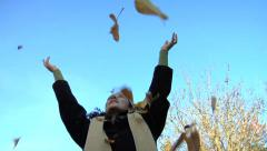 Woman throws fall leaves into air Stock Footage