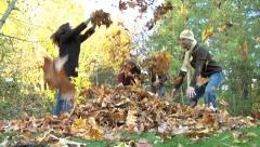 Family of four throwing leaves in air Stock Footage