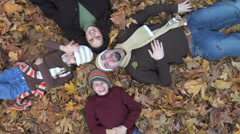 Family laying in pile of leaves - stock footage