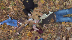 Family laying in pile of leaves Stock Footage