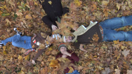 Stock Video Footage of Family laying in pile of leaves