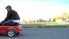 Man drining a tiny car - stock footage