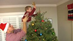 Father lifts son to put star on Christmas tree - stock footage