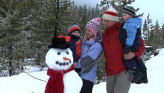Family with snowman - stock footage
