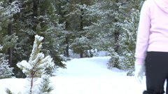 Couple walking in snowshoes kiss Stock Footage