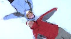 Couple laying in snow playing Stock Footage