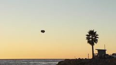 Blimp Flys Past Lifeguard Station at Sunset Stock Footage