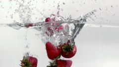 Strawberries splashing into water Stock Footage