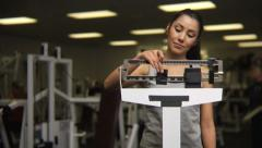 Woman on scale at a health club Stock Footage