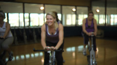 Group of women pedaling exercise bikes Stock Footage