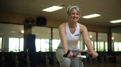 Woman on stationary bicycle - stock footage