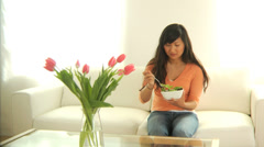 Woman in living room eating salad - stock footage