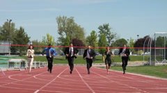 Businesspeople racing across finish line - stock footage