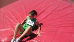 Track athlete lands on mat in high jump event - stock footage