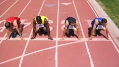 Track runners line up at start of race - stock footage