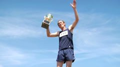 Track athlete celebrating with trophy - stock footage