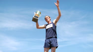 Stock Video Footage of Track athlete celebrating with trophy