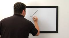 Man draws a house and family on white board Stock Footage