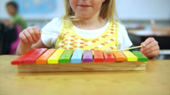 Young girl playing xylophone at school Stock Footage
