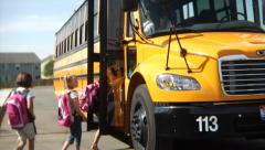 Students getting on school bus Stock Footage