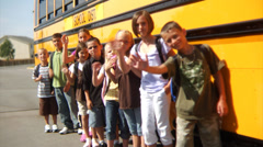 Schoolchildren waving by school bus Stock Footage