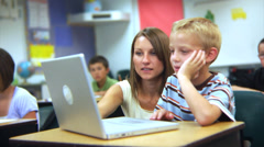 Elementary school student and teacher look at computer - stock footage