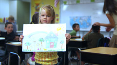 Young school girl holds up painting Stock Footage
