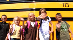 Students standing in front of school bus - stock footage